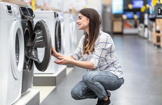 Молодая женщина в магазине выбирает стиральную машину. Бесплатные Фотографии