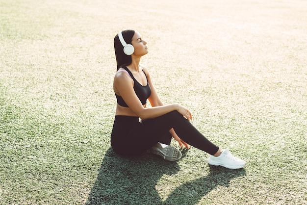 スポーツウェアの若い女性がスタジアムに座って、ヘッドフォンで音楽を聴いています。アクティブなライフスタイル Premium写真