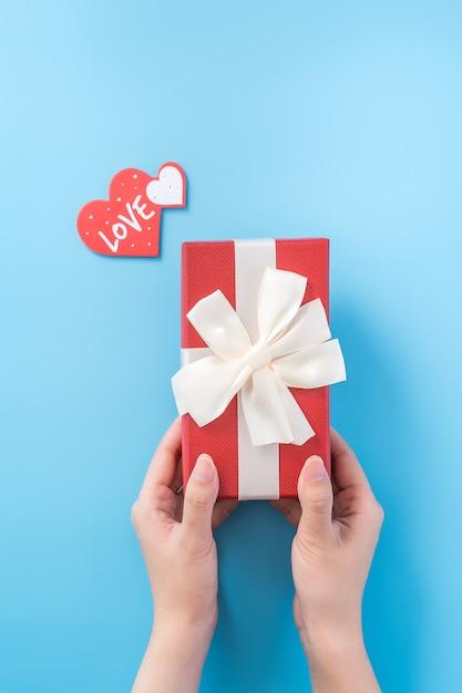 Молодая женщина делает подарок с биркой в форме сердца и текстом любви. валентина концепция Premium Фотографии