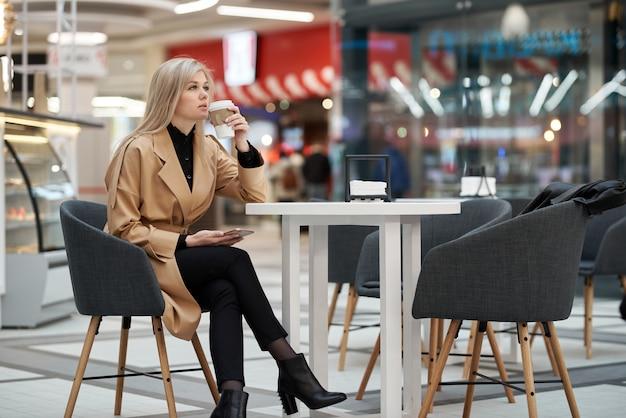 젊은 여자는 쇼핑 센터 카페에 앉아, 휴대 전화 채팅 및 그녀의 손에 커피 종이 컵을 들고. 프리미엄 사진