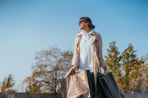 若い女性が手にバッグを持って車の中に立っています。 無料写真