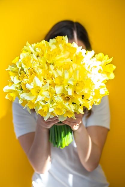 背景が黄色の若い女性は、黄色い水仙の花束で顔を覆っています。女性の日のコンセプトです。 無料写真