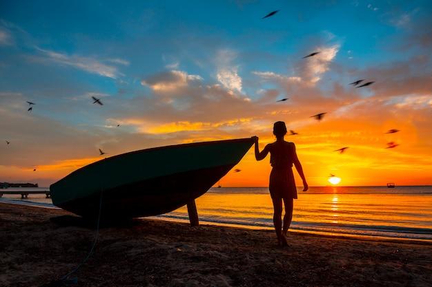 ロアタン島、ウエストエンドサンセットのボートに乗ってビーチで若い女性。ホンジュラス Premium写真