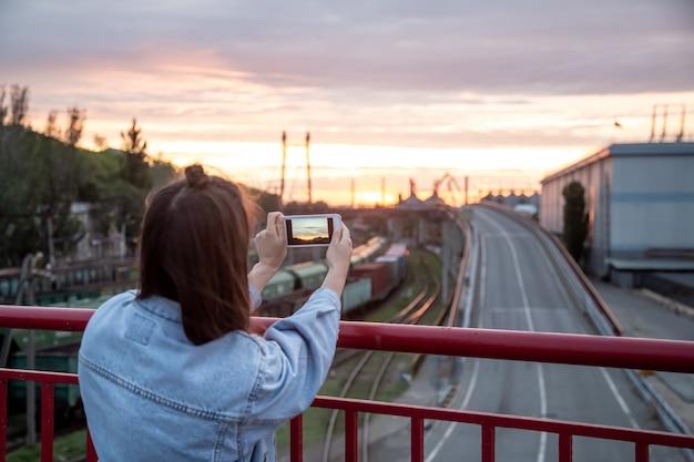 若い女性が携帯電話で橋から美しい夕日を撮影します。 無料写真