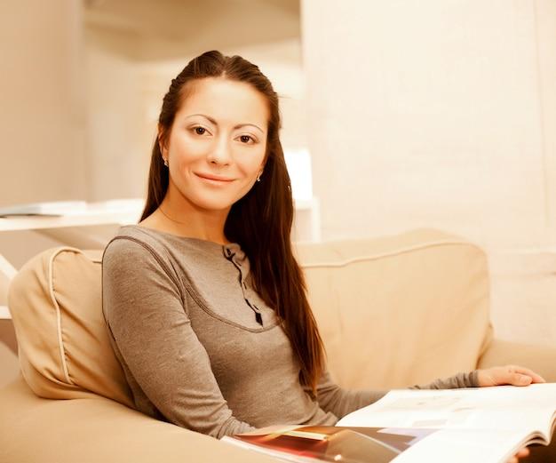 Молодая женщина читает журнал, сидя на диване Premium Фотографии