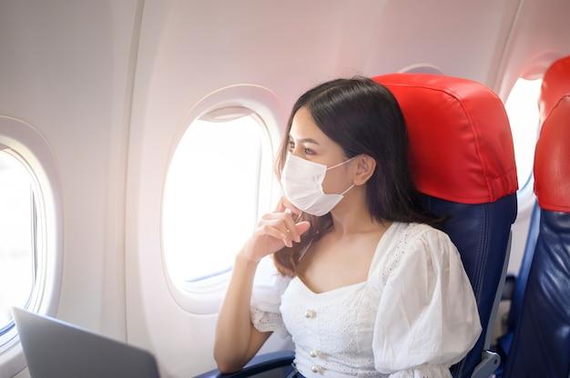 フェイスマスクを身に着けている若い女性がラップトップをオンボードで使用しています、covid-19パンデミックコンセプト後の新しい通常の旅行 Premium写真