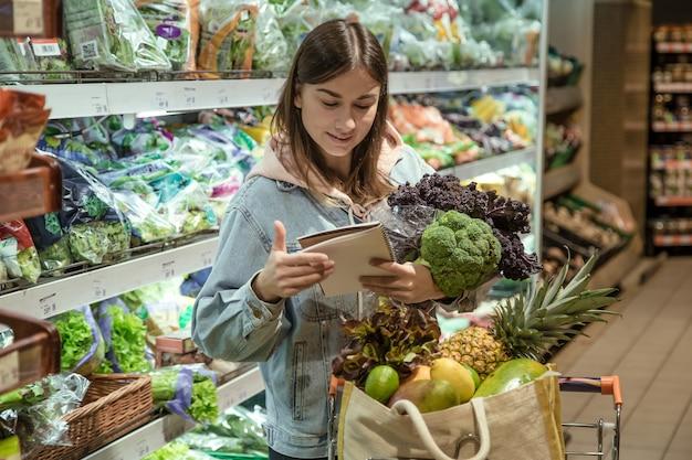 ノートを持った若い女性がスーパーマーケットで食料品を買う 無料写真