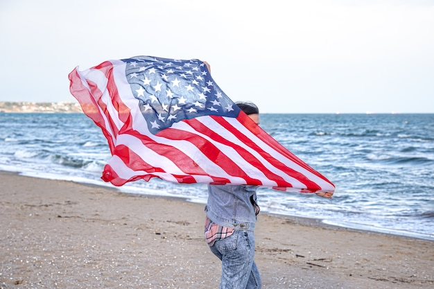アメリカの国旗を持った若い女性が海を走っています。愛国心と独立記念日のお祝いの概念。 無料写真