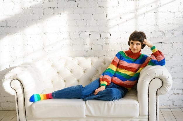 Молодая женщина с короткими волосами в радужном свитере и носках сидит на белом диване, концепция сексуальных меньшинств Premium Фотографии