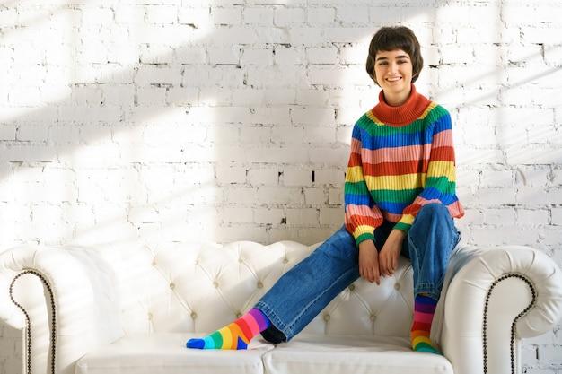 Молодая женщина с короткими волосами в радужном свитере и носках сидит на белом диване Premium Фотографии