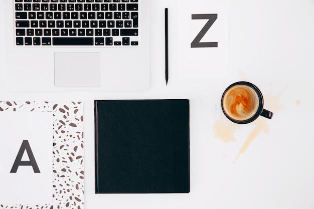 文字aとz。鉛筆;日記;ノートパソコンと白い背景の上のこぼれたコーヒーカップ 無料写真