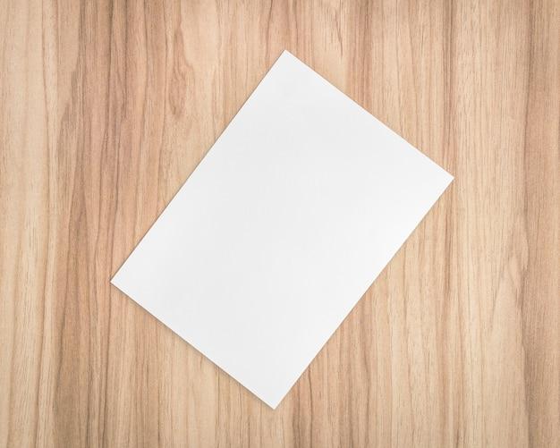 木製の背景に関するホワイトペーパーシート。 a4文書のテンプレートとテキスト用の空白スペース。 Premium写真