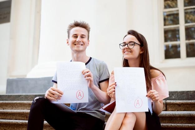 Образование, концепция университета. два подростка или студенты, проводящие тест или экзамен с оценкой a Premium Фотографии