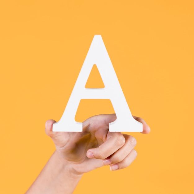 Человеческая рука держит заглавную букву a на желтом фоне Бесплатные Фотографии