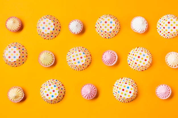 Aalaw with polka dots paper cake forms in a row on yellow background Free Photo