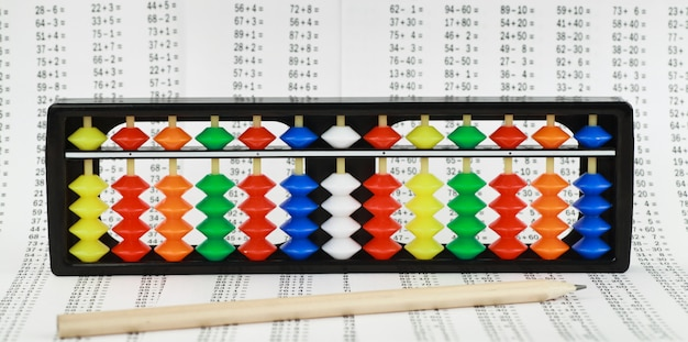 Abacus for mental arithmetic, against the background of examples to solve. Premium Photo