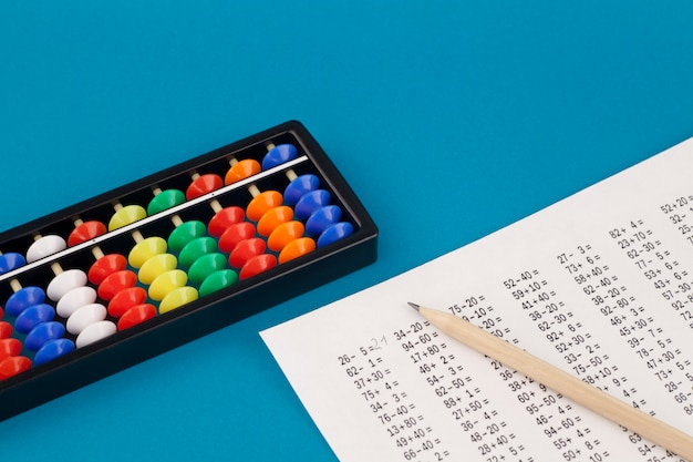 Abacus for mental arithmetic, on a blue background, with examples to solve. Premium Photo