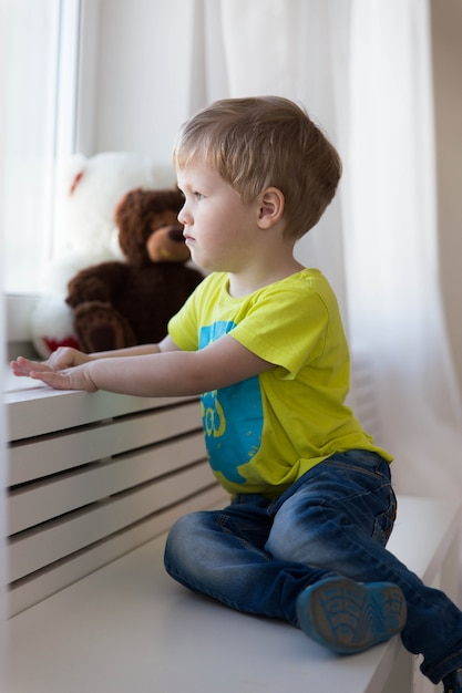Abandoned child. lonely little boy sits by the window in an orphanage Premium Photo