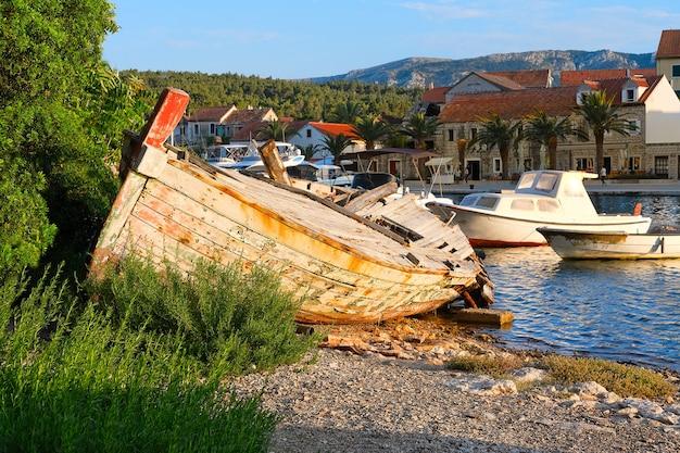 Заброшенная рыбацкая лодка на диком берегу в деревне врбоска на хваре, далмация, хорватия, европа. Premium Фотографии