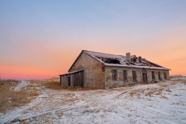 북극 하늘을 배경으로 버려진 집. Teriberka의 오래된 정통 마을 프리미엄 사진