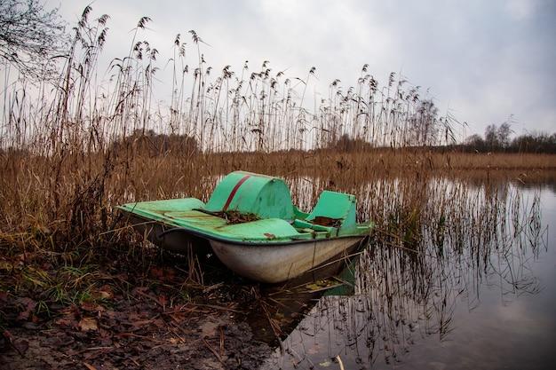 Заброшенная ржавая весельная лодка у озера в грязной местности Бесплатные Фотографии