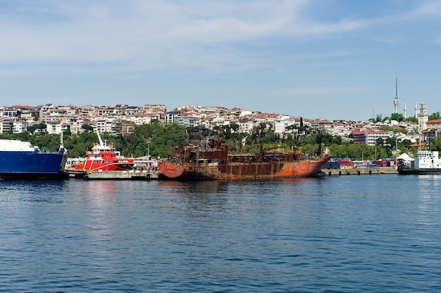 Заброшенный ржавый корабль возле береговой линии Premium Фотографии