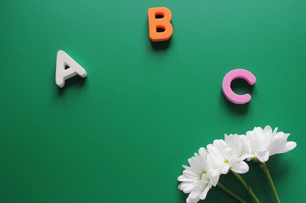 Abc  - 英語のアルファベットの最初の文字と3つの白い菊 Premium写真