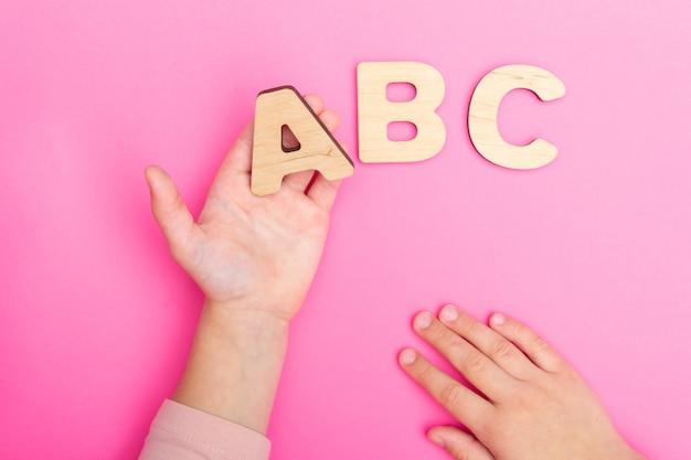 Буквы abc в руках ребенка на розовом фоне Premium Фотографии