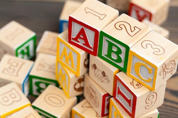 木製のテーブルにアルファベットブロックabc。 Premium写真
