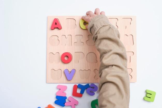 Птичьего полета дошкольника, детский сад мальчик играет с алфавит блоков, дети учат английский язык с деревянными развивающие головоломки игрушки abc Premium Фотографии