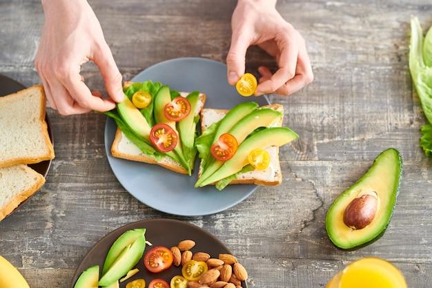 Выше вид крупным планом неузнаваемой молодой женщины, делающей бутерброды с авокадо на здоровый завтрак, копией пространства Premium Фотографии