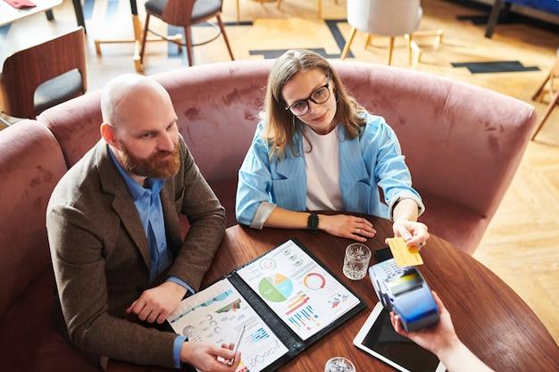 財務報告書を持ってテーブルに座ってレストランでスマートフォンで支払うビジネスマンの上のビュー Premium写真