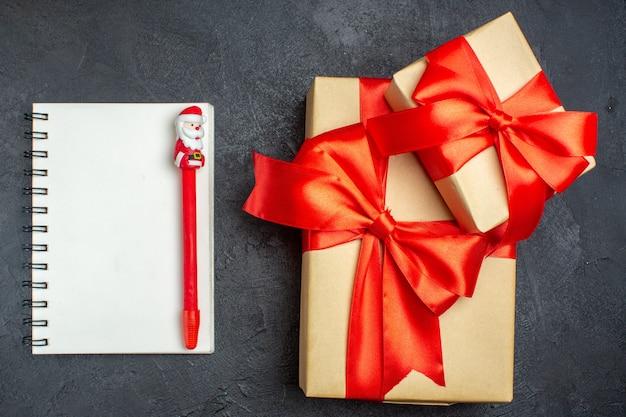 Выше вид на рождественский фон с красивыми подарками с бантовой лентой и блокнотом с ручкой на темном фоне Бесплатные Фотографии