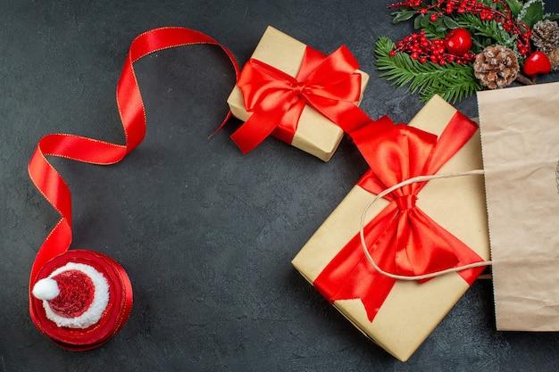 暗い背景に美しい贈り物モミの枝針葉樹の円錐形の赤いリボンとクリスマス気分のビューの上 無料写真