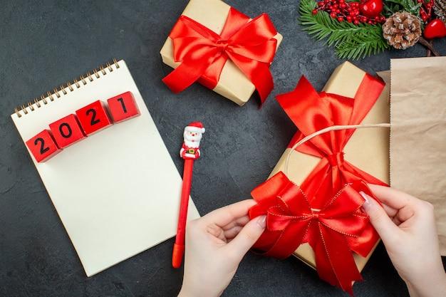 Выше вид рождественского настроения с красивыми подарками с красной лентой и цифрами на блокноте с ручкой на темном столе Бесплатные Фотографии