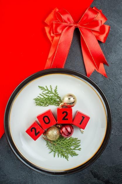 Выше вид номеров аксессуаров украшения на тарелке и красной ленте на темном столе Бесплатные Фотографии
