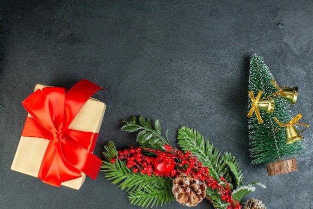 黒の背景に弓形の赤いリボンモミの枝針葉樹の円錐形のクリスマスツリーとギフトボックスのビューの上 無料写真