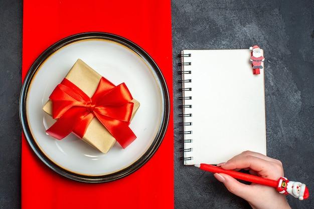 Выше, вид на национальный рождественский фон еды с подарком с красной лентой в форме банта на пустых тарелках на красной салфетке и рукой, держащей ручку на блокноте на черном фоне Бесплатные Фотографии