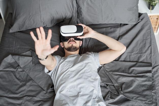 Выше вид молодого бородатого мужчины, погруженного в виртуальную реальность, лежащего на кровати и смотрящего видео в очках виртуальной реальности. Premium Фотографии