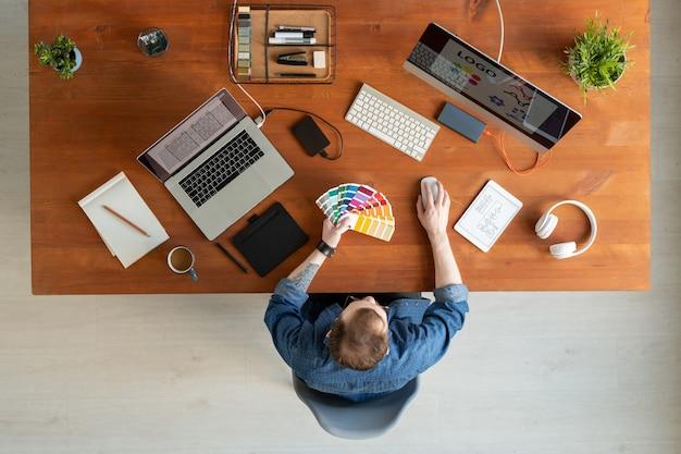 Выше вид молодого человека в джинсовой рубашке, выбирающего цвет на образце во время работы над фирменным стилем компании. Premium Фотографии