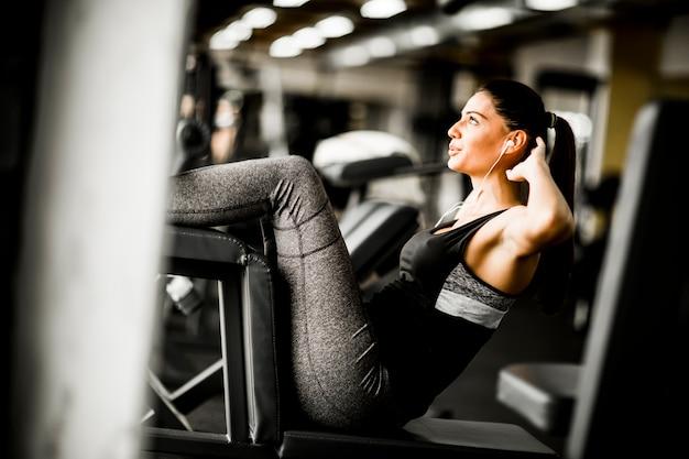 Молодая женщина упражнения abs в тренажерном зале Premium Фотографии