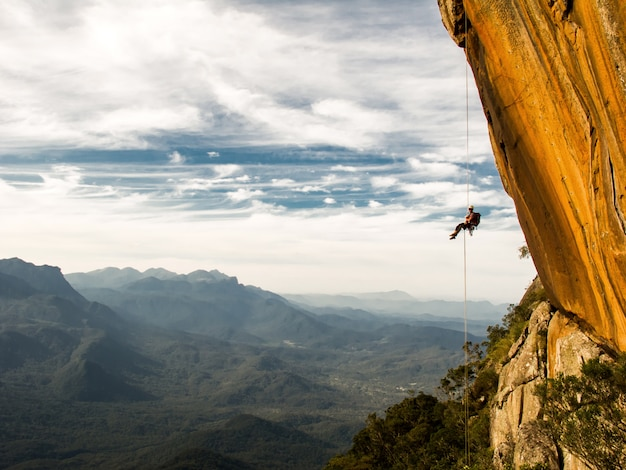 Abseiling a negative yellow rock wall with mountains Premium Photo