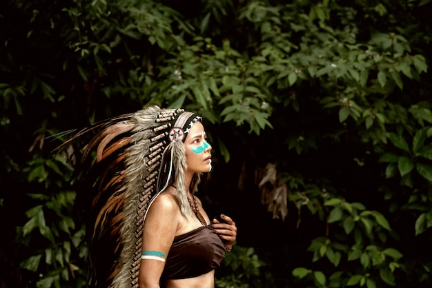 The abstract art design background of beautiful woman wearing headdress feathers of birds. Premium Photo