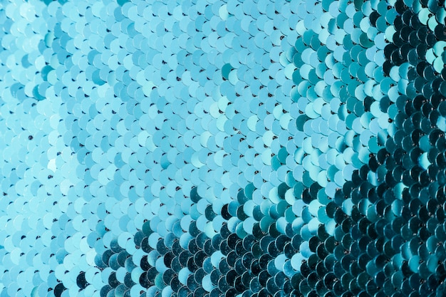 Abstract background with blue sequins color on the fabric. texture scales of round sequins with color transition. Premium Photo