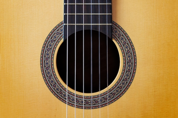 Abstract background wooden spanish classic guitar hole with nylon string on Premium Photo