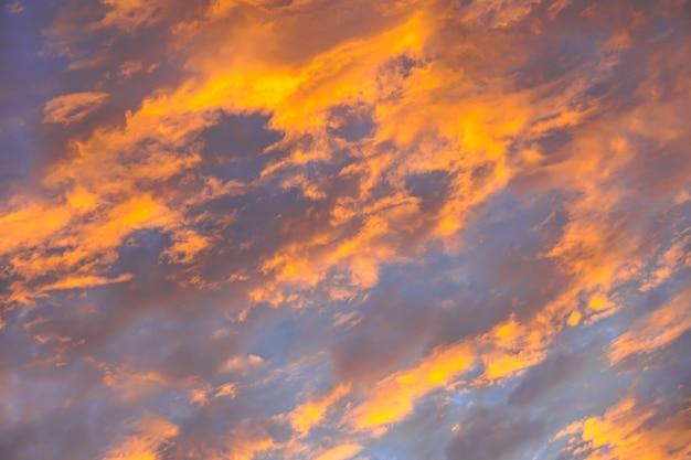 日の出の空に抽象的な美しいオレンジ色のふわふわの雲-カラフルな自然の空のテクスチャの背景 無料写真