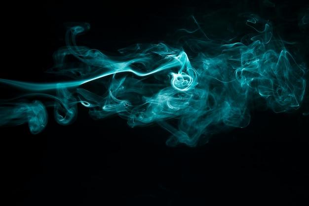 Il fumo blu astratto si muove su fondo nero Foto Gratuite