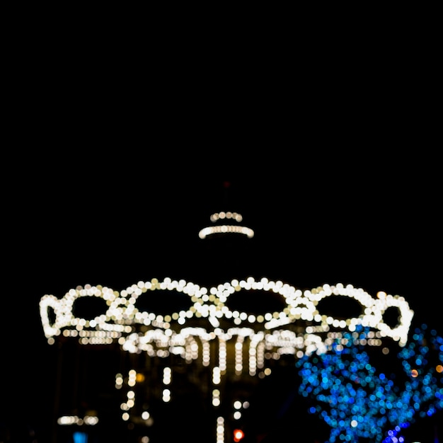 Abstract blurred background of vintage carousel at night Free Photo