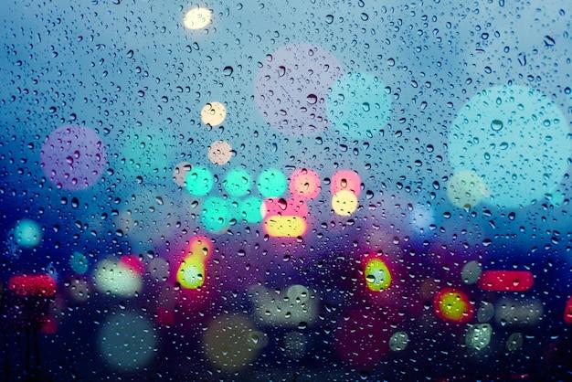 雨の中で軽い車からボケ味を持つ抽象的な背景をぼかした写真 Premium写真