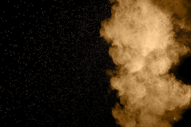Abstract brown dust explosion on  black background. Premium Photo